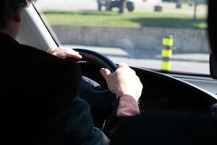 Man driving a car with hands on steering wheel Stock Photo