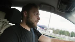 Man driving a car. Handsome man with a beard in a black T-shirt drives his car. Traveling by car. stock footage