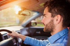 Man driving a car. Handsome young man in a blue shirt driving a car Stock Photography