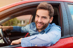 Man driving a car. Handsome young man in a blue shirt driving a car Stock Photos
