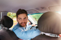 Man driving a car. Handsome young man in a blue shirt driving a car Stock Images