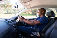 Man driving car. Happy young african american man driving a car Royalty Free Stock Image