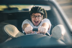 Man driving car in helmet with horror on her face Stock Image