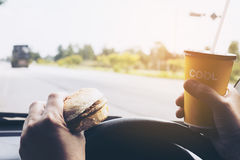 Man driving car while holding a cup of cold coffee and eating hamburger. Dangerously Stock Images