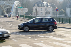 Man driving car in intersection. MULHOUSE, FRANCE  - DEC 19, 2016: Man driving car in town with large mettalic suspended bridge in the background Royalty Free Stock Images