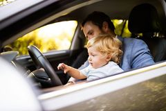 Man driving a car with little son. Stock Images