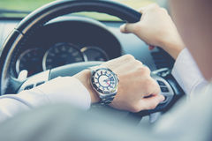 Man driving a car and looking at watch. Business concept Stock Images