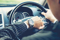 Man driving a car and looking at watch Stock Images
