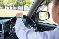 Man driving a car and looking at watch Royalty Free Stock Image