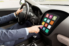 Man driving car with menu icons on board computer Royalty Free Stock Photo