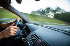 Man driving a car moving fast on a highway. Motion blurred image royalty free stock image