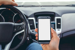 A man driving a car with  phone. Young man driving a car with a phone in his hand. Multitasking. Don't text and drive Stock Photography