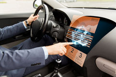 Man driving car and pointing to on-board computer Stock Photos