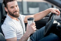 Man driving a car. Portrait of a handsome man dressed cassual in white t-shirt driving a car with coffee to go Royalty Free Stock Images