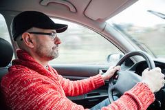 Man driving a car in a rainy day. Concentrated man with cap and glasses driving his car in a rainy day Royalty Free Stock Images