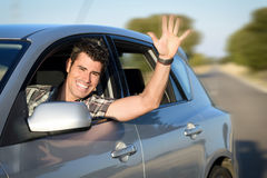 Man driving car on road. Man in car driving and waving. Male driver having fun traveling on road trip Stock Photo