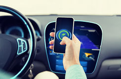 Man driving car and setting eco mode on smartphone. Transport, business trip, technology and people concept - close up of man driving car and setting eco mode on Stock Images