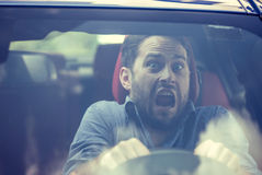 Man driving a car shocked about to have traffic accident, windshield view. Young man driving a car shocked about to have traffic accident, windshield view stock image