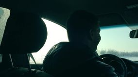 Man is driving a car silhouette winter. view from the inside of the car man outdoors movement along the road stock footage