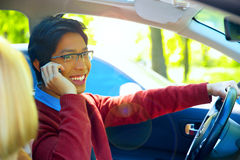 Man driving car and speaking on mobile phone. Young happy man driving car and speaking on mobile phone Royalty Free Stock Image