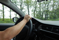 Man driving the car at speed. Hands of car driver on steering wheel Stock Photo