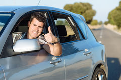 Man driving car. Successful man driving car and doing thumbs up. Cheerful male driver approving Stock Photo