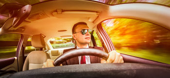Man driving a car. Man in a suit and sunglasses driving on a road in the car Stock Photos