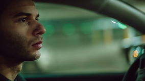 A man driving the car at undergroung parking. Close up. Bokeh background stock video footage