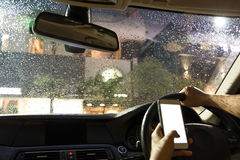 Man driving car and using cell phone while raining at night. Selected focus on rain water drop on windshield man driving car and using cell phone while raining Stock Images