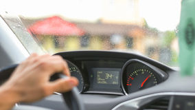 Man Driving a Car Through the Village. Caucasian man driving a car and placing his hand slowly on the wheel Stock Photo
