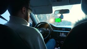A man driving a car in the winter. Smartphone has a green screen attached to the windshield. Chrome key, slow motion stock video footage
