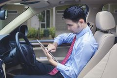 Man driving checks digital tablet for locating an address.  Royalty Free Stock Image