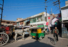 Man driving cycle past retro transport on the indian street Stock Photos