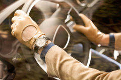 Man driving, detail shot. Hands on the steering wheel, wearing leather men gloves Stock Photos