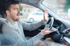 Man caused an accident distracted by his mobile phone. Man driving distracted by his smartphone causes a car crash Stock Images