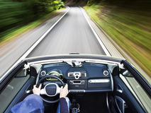 Man driving a electric car. Motion blur shot of a young man driving a electric car Stock Image