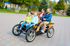 Man driving family in pedal car. Pretty family having fun in spring park: bearded middle-aged father driving orange quadricycle pedal car while his joyful family Royalty Free Stock Image
