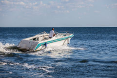 Man driving a fast boat Stock Image