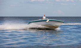 Man driving a fast boat Stock Photos