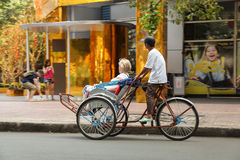 A man is driving a foreigner by pedicab on the center of Saigon (Ho Chi Minh City ) Vietnam on traditional TET holiday ( Lunar new Stock Image