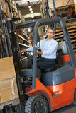 Man Driving Fork Lift Truck In Warehouse. Working Stock Photography