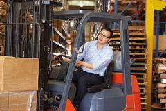 Man Driving Fork Lift Truck In Warehouse. Working Royalty Free Stock Images