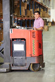Man Driving Fork Lift Truck In Warehouse. Smiling To Camera Stock Photos