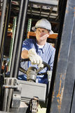 Man Driving A Forklift. Confident male industrial worker driving a forklift at workplace Royalty Free Stock Images