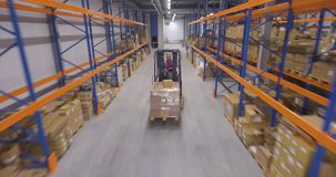 Man driving forklift truck in warehouse. Moving shot stock video footage
