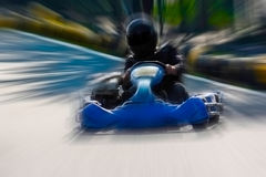 A man is driving Go-kart with speed in the park. A man is driving Go-kart with speed in the park on karting track - front view Stock Images