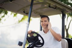A man is driving a golf car and talking to someone on a smartphone. A man in a white suit is sitting at the wheel of a golf car and talking to someone on his stock photo