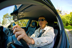 A Man Driving his Car. A man wearing sunglasses driving in his  new car Stock Images