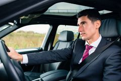 Man driving in his car in business attire. Man driving his car for business travel wearing a suit stock images