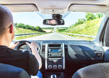 The man is driving his car with hands on the steering wheel. Long highway (highroad) is in the sunny summer day. Active caucasian male model. Travel (vacations Stock Photography